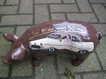 Sparschwein mit Portrait und Oldtimer